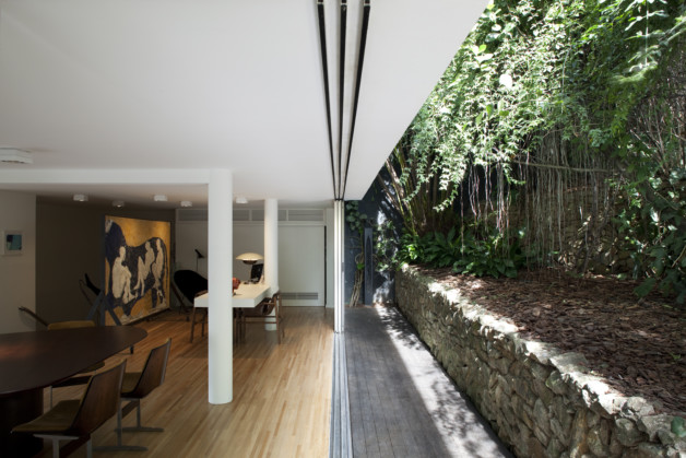View of the dining room and backyard of Arthur Casas' home, designed by João Batista Vilanova Artigas in 1943.